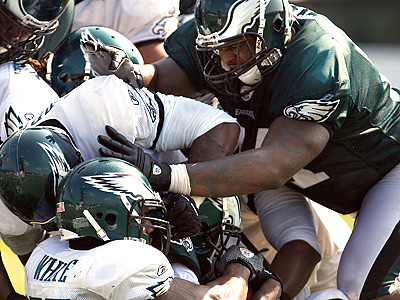 Jason Peters, right, tries to push Akeem Jordan and Tracy White out of the way during practice. (David Maialetti / Staff Photographer)