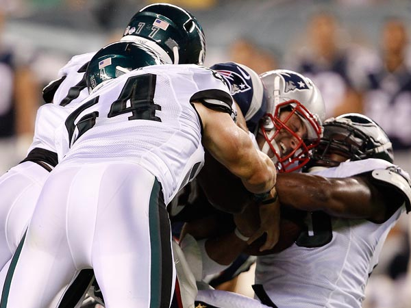 Tim Tebow is sacked by the Eagles´ Jake Knott and Vinny Curry. (David Maialetti/Staff Photographer)