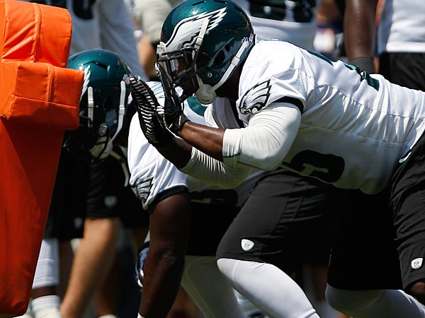 Vinny Curry, center, prepares to hit the blocking sled during training camp. (David Maialetti/Staff Photographer)