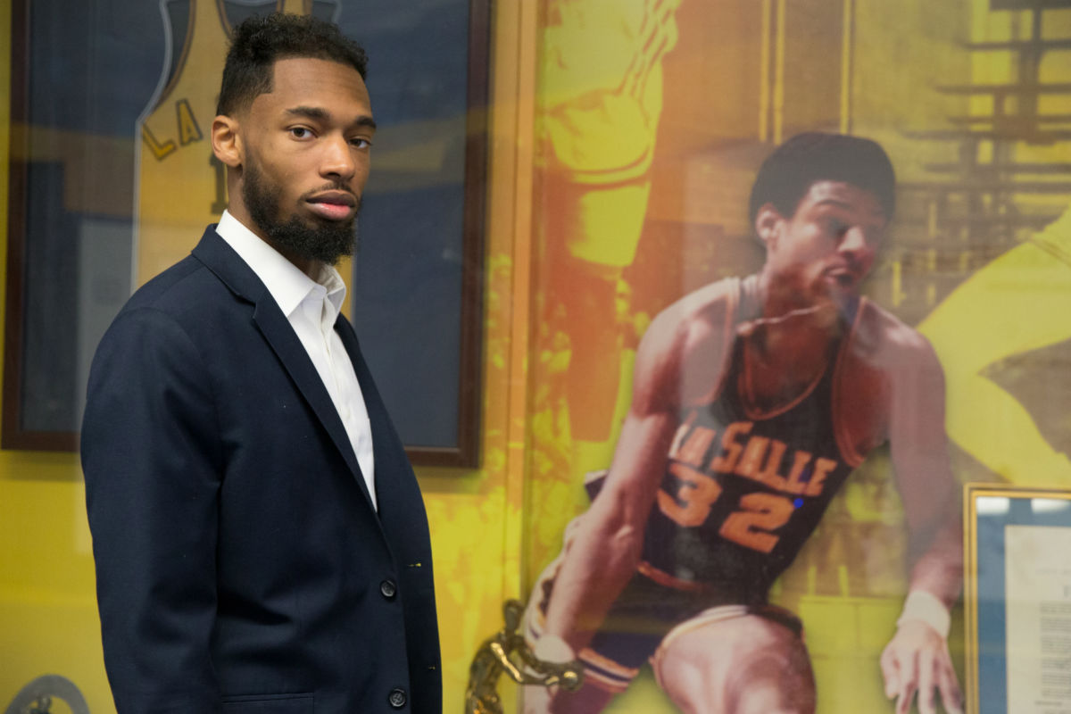 In a visit to La Salle University in February, Michael Johnson-Brooks stands before a photo of his father at a display honoring Explorers greats.