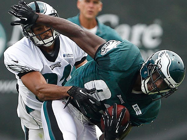Curtis Marsh, left, hits Jason Avant after he catches a pass during<br />training camp. (David Maialetti/Staff Photographer)