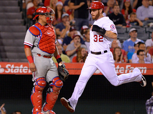 Josh Hamilton, right, scores on a single by Howie Kendrick as Philadelphia Phillies catcher Carlos Ruiz looks on during the sixth inning of a baseball game, Wednesday, Aug. 13, 2014, in Anaheim, Calif. (Mark J. Terrill/AP)