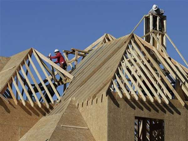 Workers install a roof on a home under construction in Charlotte, N.C . (AP Photo / Chuck Burton)
