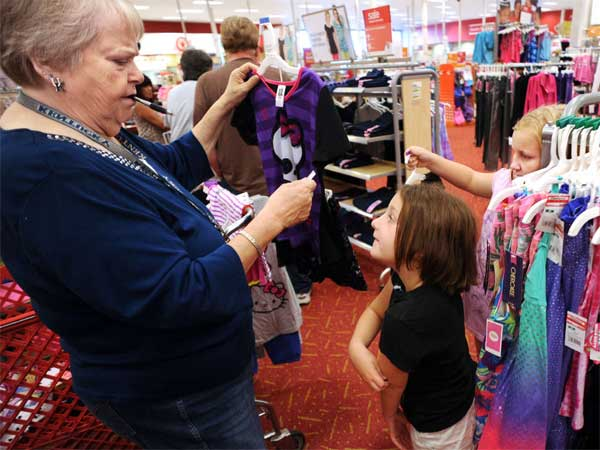 Alissa Trogden, 6, watches as Nora Crowe checks the size and price of a top at a Target in Owensboro, Ky. (GARY EMORD-NETZLEY / Messenger-Inquirer)