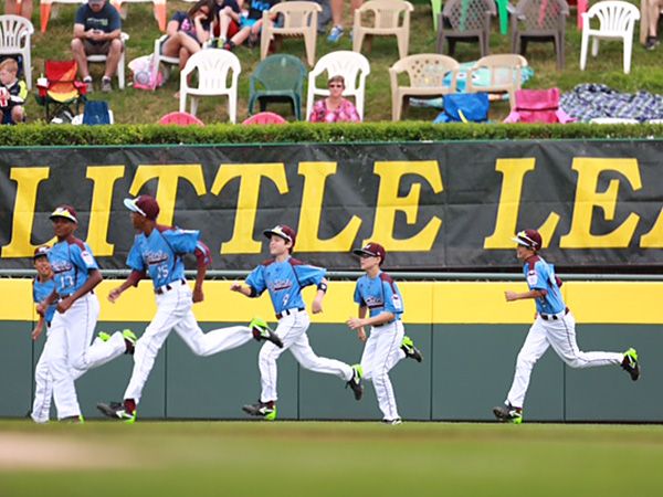 Taney players run onto the field in Williamsport, Pa. before their first game of the 2014 Little League World Series. (David Swanson/Staff Photographer)
