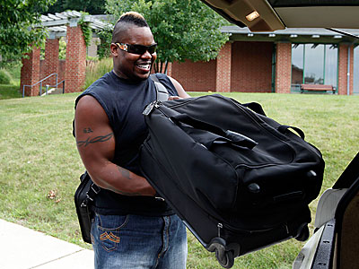 "Shawn Andrews unloads his luggage on the first day of training camp. Today, Andrews attacked the media for portraying him as ""crazy."" (AP Photo)"