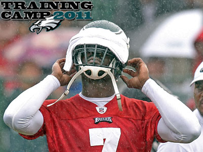 Michael Vick covers his helmet during a downpour on the last day of Eagles training camp. (Steven M. Falk/Staff Photographer)