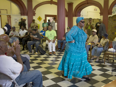 Sacaree Rhodes, of The African Daughters of Fine Lineage, arrives to the applause of a small gathering at a meeting in support of Arlene Ackerman on Tuesday at the Kingsessing Recreation Center. (David M Warren / Staff Photographer)