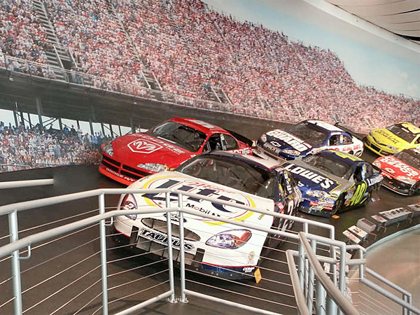 The opening display at the NASCAR Hall of Fame museum in Charlotte, N.C., shows the banked track. As you walk, the bank gets steeper. (Philippa Chaplin/Staff)