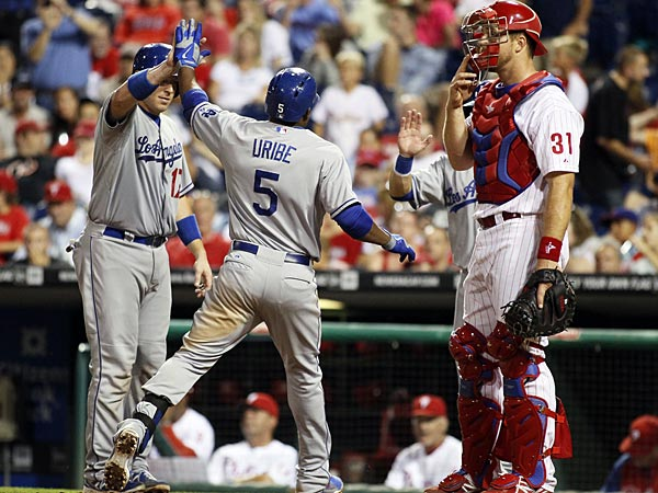 Los Angeles Dodgers´, A.J. Ellis, high-fives Juan Uribe as Skip Schumaker, obscured from view at right by Philadelphia Phillies catcher Erik Kratz, waits to celebrate Uribe´s three-run home run in the ninth inning of a baseball game with the Philadelphia Phillies, Saturday, Aug. 17, 2013, in Philadelphia. The Dodgers won 5-0. (AP Photo/Tom Mihalek)