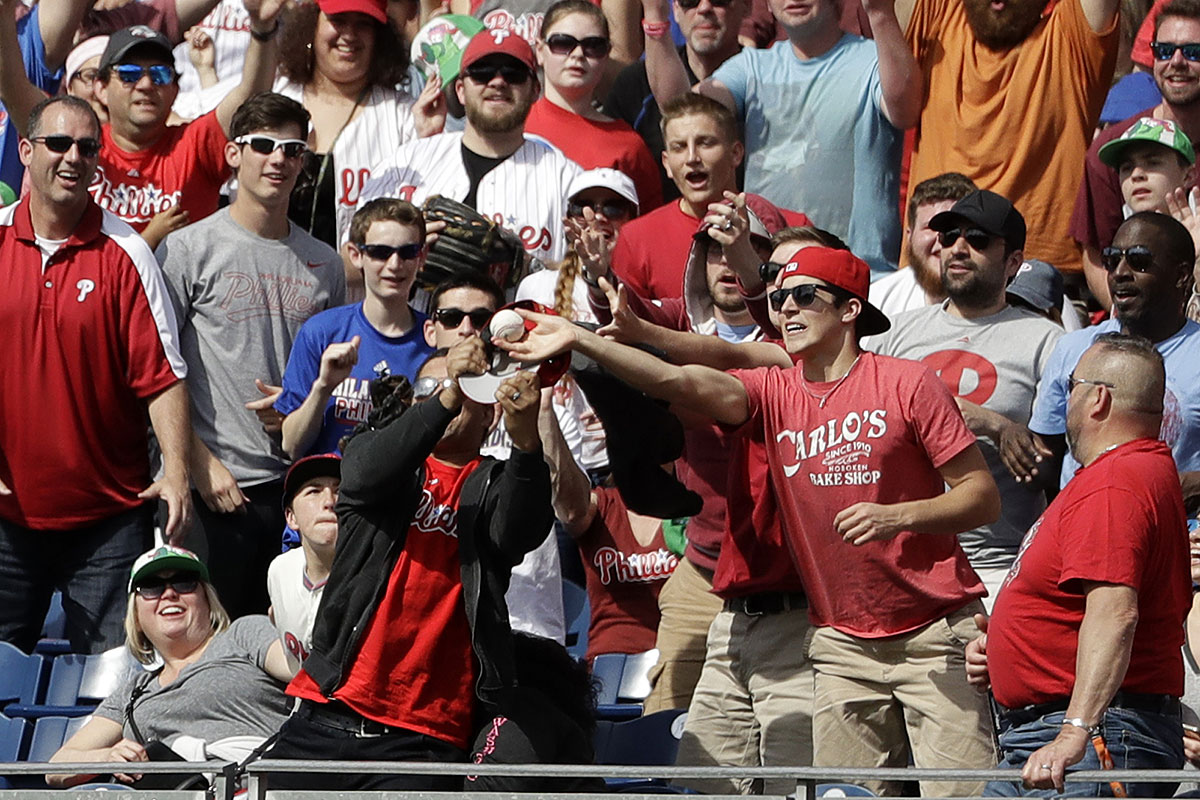 Fans try to catch a two-run home run hit by Philadelphia Phillies´ Cesar Hernandez during the eighth inning of a baseball game against the Atlanta Braves, Sunday, April 23, 2017, in Philadelphia. Philadelphia won 5-2.
