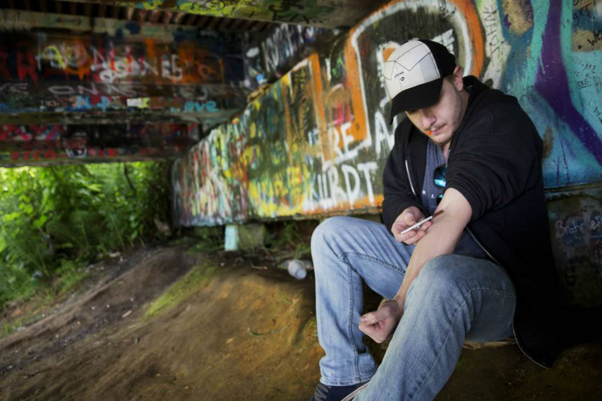 Forrest Wood, 24, injects heroin into this arm under a bridge along the Wishkah River at Kurt Cobain Memorial Park in Aberdeen, Wash., Tuesday, June 13, 2017. Wood grew up here, watching drugs take hold of his relatives, and he swore to himself that he would get out of this place, maybe spend his days in the woods as a park ranger. But he started taking opioid painkillers as a teenager, and before he knew it he was shooting heroin, a familiar first chapter in the story of American addiction.