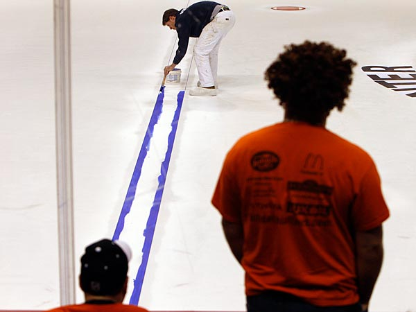 Fans watch as painter Philip Hamilton paints one of the blue lines for the upcoming Flyers season at the Wells Fargo Center. (David Maialetti/Staff Photographer)