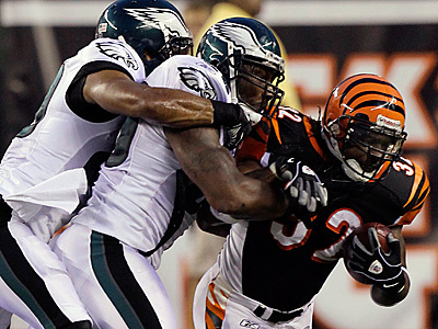 Bengals running back Cedric Benson (32) is tackled by Eagles safety Nate Allen, left, and linebacker Akeem Jordan. (AP Photo/Ed Reinke)