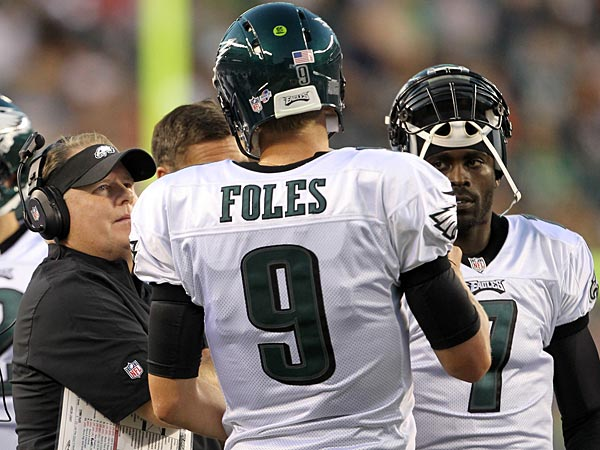 Eagles head coach Chip Kelly (left) talks to quarterbacks Nick Foles (center) and Michael Vick (right). (Yong Kim/Staff Photographer)