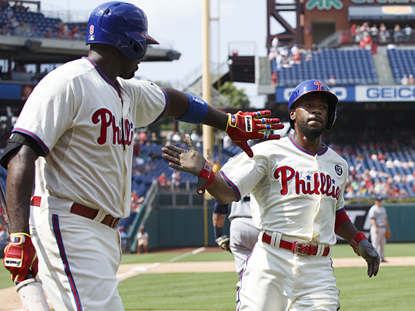 Jimmy Rollins, right, celebrates his run with Ryan Howard, left, on a single by Chase Utley during the fifth inning against the Seattle Mariners on Wednesday, Aug. 20, 2014, in Philadelphia. (Chris Szagola/AP)