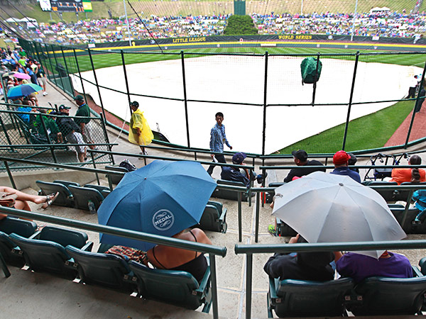 Fans hide under umbrellas after a tarp is placed over the infield at Howard J. Lamade Stadium in Williamsport, Pa. on Wednesday afternoon. (Michael Bryant/Staff Photographer)