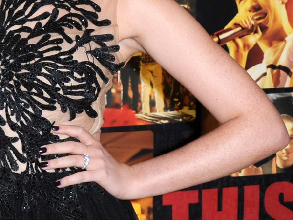 """Perrie Edwards of Little Mix wears a diamond ring as she attends the UK Premiere of ´One Direction: This Is Us ´  on Tuesday Aug. 20, 2013, in London. One Direction has one less eligible bachelor. Band member Zayn Malik is engaged to Perrie Edwards of the group Little Mix. Edwards was photographed wearing a diamond ring at the premiere of the One Direction film . Edwards´ mother, Debbie, confirmed Wednesday that her daughter and Malik were engaged. She told Real Radio: """"It´s true. They got engaged on Sunday and it´s absolutely lovely."""" (Photo by Jon Furniss photography /Invision/AP Images)"""