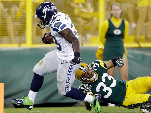 Seahawks´ Christine Michael breaks away from Green Bay Packers´ Micah Hyde for a touchdown run during the second half of an NFL preseason football game Friday, Aug. 23, 2013, in Green Bay, Wis. (Jeffrey Phelps/AP)
