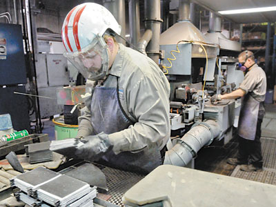 Bill Galbreath (left) and James Cribbs (right) prepare lead battery core elements at Axion Power in New Castle. (Bob Donaldson / Post-Gazette)