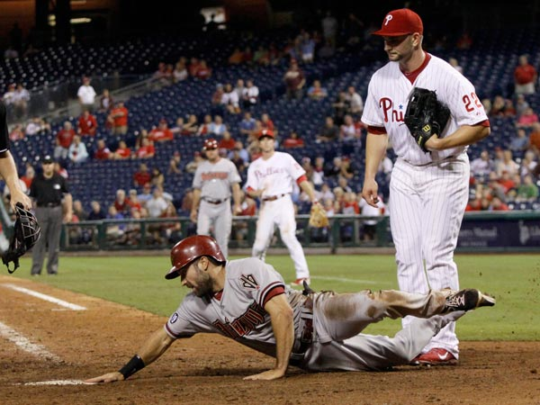 Diamondbacks´ Adam Eaton scores as Philadelphia Phillies´ pitcher Casper Wells watches in the eighteenth inning of an MLB National League baseball game Saturday, Aug. 24, 2013, in Philadelphia. The Diamondbacks won 12-7. (H. Rumph Jr/AP)