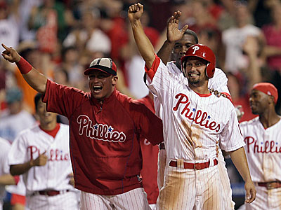 Carlos Ruiz, left, Shane Victorino and Ryan Howard wait for Pedro Feliz to round the bases after his three-run walkoff home run against the Dodgers last night. (Yong Kim / Daily News)