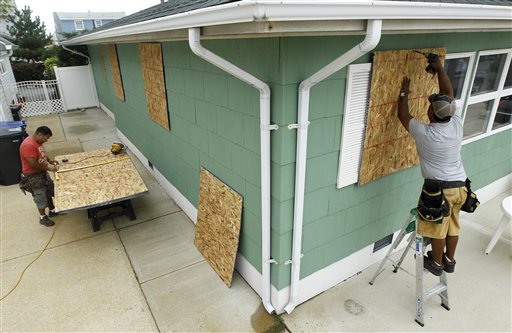 Ismael Ramirez, right, drills a plywood board on a home an Ortley Beach, N.J., as his brother Jorge Ramirez measures a board as the handymen work on boarding up a home for a New Jersey Shore resident in preparation for Hurricane Irene. (AP Photo/Julio Cortez)