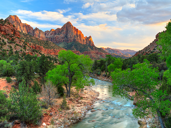 If you're planning an outdoorsy adventure during Labor Day weekend, you'll need to know which national park is the best for biking, hiking, camping, or fishing. (Zion Canyon via iStock)