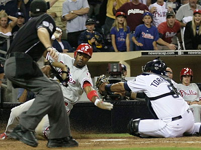 The Phillies´ Jimmy Rollins scores as Padres catcher Yorvit Torrealba misses the tag. (AP Photo/Gregory Bull)