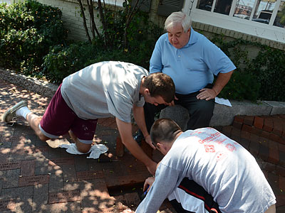 Tavern owner Pat Daugherty watches as two of his servers remove a brick with Jerry Sandusky´s name on it. (Emily Kaplan/Staff)