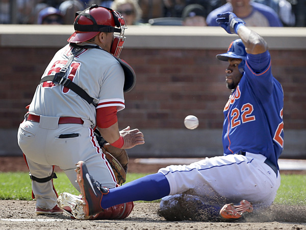 New York Mets´ Eric Young Jr., right, slides safely home before the ball reaches Philadelphia Phillies catcher Carlos Ruiz during the sixth inning of the baseball game at Citi Field Thursday, Aug. 29, 2013 in New York. (AP Photo/Seth Wenig)
