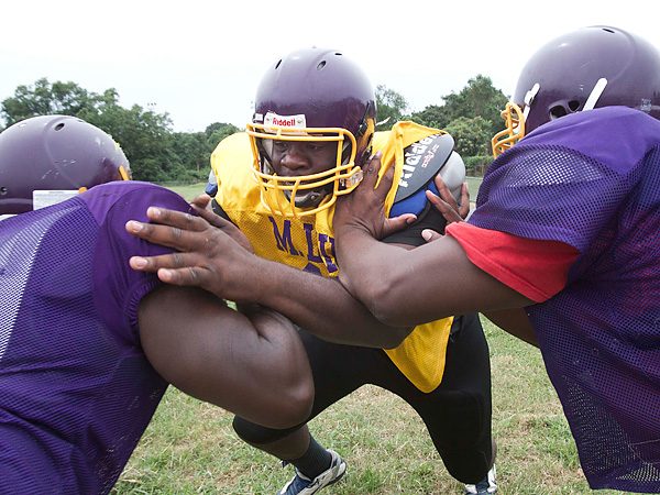 Martin Luther King Jr. H.S. lineman Dontae Angus breaks the blocks of<br />teammates Darvis Hurst-Rodney (left) and Frank Darden at practice. (David M Waren/Staff Photographer)