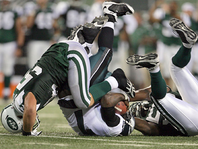 Michael Vick gets sacked by Jamaal Westerman (right) and Kenwin Cummings of the Jets during the fourth quarter last night.  (Yong Kim / Staff Photographer)