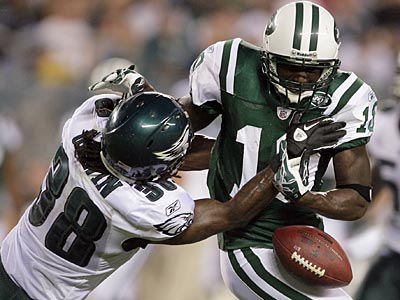Eagles Jorrick Calvin strips the ball from Jets receiver Santonio Holmes on Thursday. (Yong Kim/Staff Photographer)