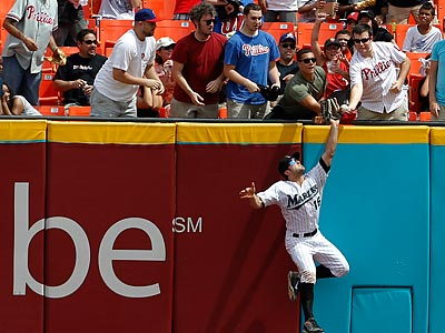 Fans interfere with the Marlins´ Bryan Peterson as he attempts to catch Hunter Pence´s drive in the sixth inning. (Lynne Sladky/AP)