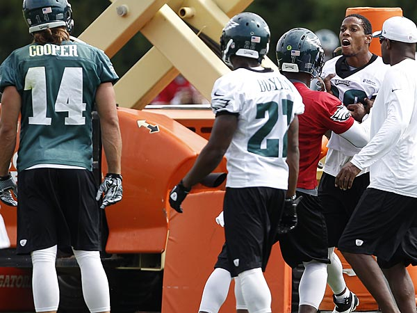 Michael Vick holds back Cary Williams, right, after he locked up with Riley Cooper, left, during Eagles practice on September 5, 2013. (David Maialetti/Staff Photographer)