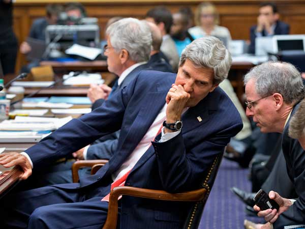 Secretary of State John Kerry confers with U.S. Ambassador to Syria Robert Ford, right, on Capitol Hill in Washington, Wednesday, Sept. 4, 2013, during a House Foreign Affairs Committee hearing on President Barack Obama´s request for congressional authorization for military intervention in Syria. (AP Photo)