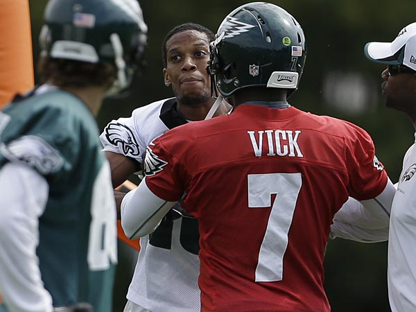 Eagles quarterback Michael Vick (7) restrains Cary Williams from Riley Cooper during practice on Thursday. (Matt Rourke/AP)