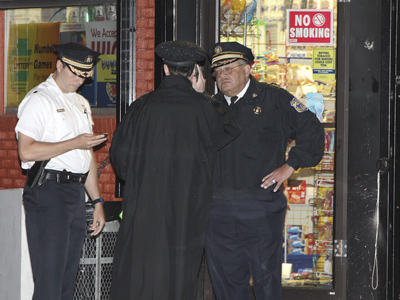 Police Commissioner Charles Ramsey, right, talks with officers at the scene where three were shot dead in a grocery store. (Steven M. Falk / Staff Photographer)