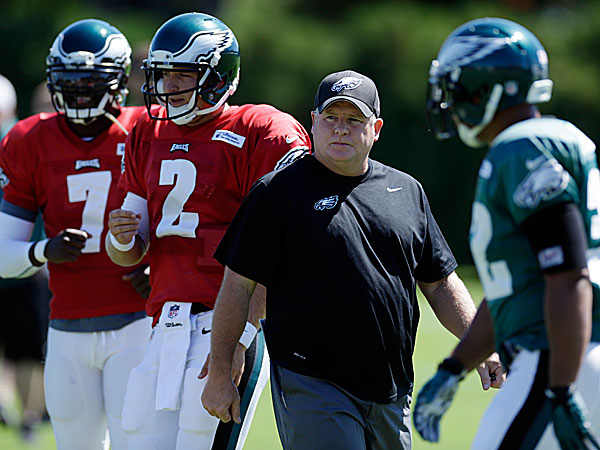 Eagles head coach Chip Kelly directs practice as quarterbacks Michael Vick and Matt Barkley run a drill. (Matt Rourke/AP)
