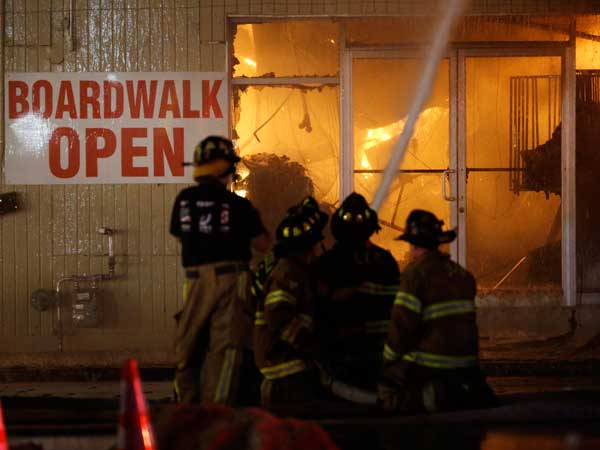 Firefighters battle a blaze in a building on the Seaside Park boardwalk on Thursday, Sept. 12, 2013, in Seaside Park, N.J. The fire began in a frozen custard stand on the Seaside Park section of the boardwalk and quickly spread north into neighboring Seaside Heights. (AP Photo/Julio Cortez)