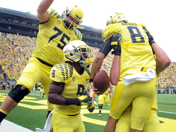Oregon quarterback Marcus Mariota (8) is mobbed by teammates after scoring a touchdown during the second quarter of the NCAA college football game against the Tennessee in Eugene, Ore., Saturday, Sept. 14, 2013. (Steve Dykes/AP)