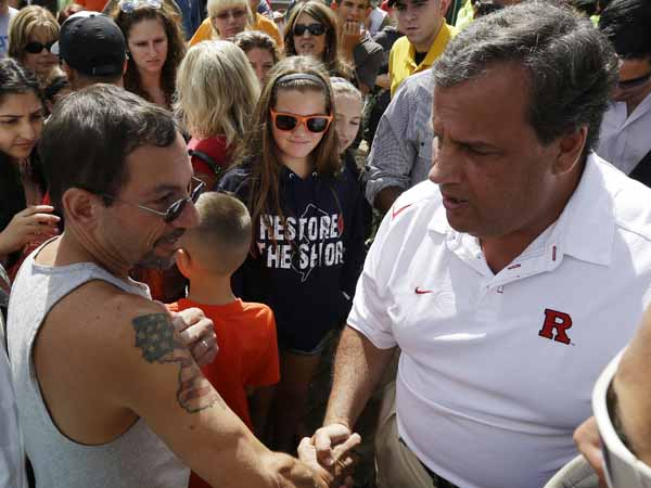 Pete Bachella of Ringwood, N.J., displays his New Jersey map tattoo to New Jersey Gov. Chris Christie during a visit Saturday to the Seaside Park boardwalk two days after a massive fire burned a large portion of the boardwalk. (AP Photo/Julio Cortez)