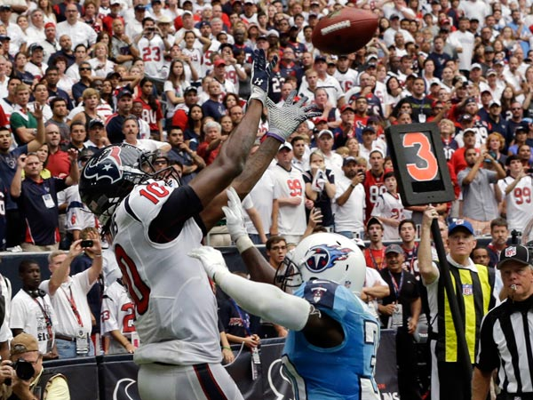 Texans´ DeAndre Hopkins (10) catches the winning touchdown over Tennessee Titans´ Jason McCourty, right, during overtime of an NFL football game on Sunday, Sept. 15, 2013, in Houston. (David J. Phillip/AP)