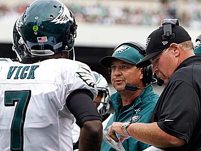 Andy Reid and Marty Mornhinweg discuss strategy with Michael Vick during Sunday´s win. (David Maialetti/Staff Photographer)