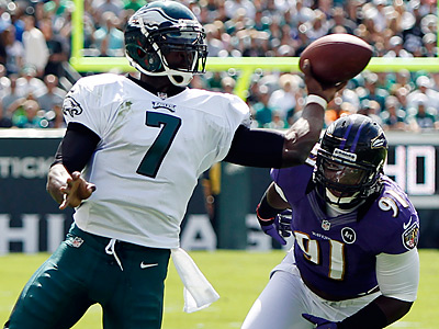 Michael Vick is pursued by Ravens linebacker Courtney Upshaw. (Mel Evans/AP Photo)