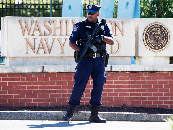 An armed officer who said he is with the Department of Defense, works near the gate at the Washington Navy Yard, closed to all but essential personnel, in Washington, on Tuesday, Sept. 17, 2013, the day after a gunman launched an attack inside the Washington Navy Yard on Monday, spraying gunfire on office workers in the cafeteria and in the hallways at the heavily secured military installation in the heart of the nation´s capital. (AP Photo/Jacquelyn Martin)
