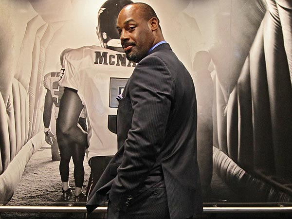 Donovan McNabb looks like he is ready to run put onto the field one more time as he poses in front of a photo of himself in an elevator at Lincoln Financial Field. (Michael Bryant/Staff Phtographer )