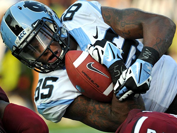 North Carolina tight end Eric Ebron (85) is tackled after a reception by South Carolina´s Kadetrix Marcus (25) and Brison Williams (12) during the first half of an NCAA college football game, Thursday, Aug. 29, 2013, in Columbia, S.C. (AP Photo/Stephen Morton)