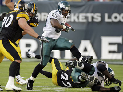 Brian Westbrook tries to leap over teammate Tra Thomas but landed on him and was injured during the second quarter Sunday. (Ron Cortes / Inquirer)